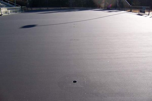 After the concrete has properly cured and the existing court surface is thoroughly cleaned, the enti
